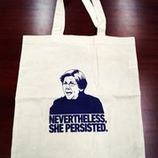 White bag with black writing reading Nevertheless she persisted.