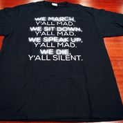 Black t-shirt with white letters reading We march. Y'all mad. We sit down.  Y'all mad. We speak up. Y'all mad. We die. Y'all silent.